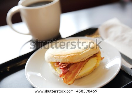 Bacon and fried egg roll with coffee