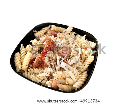 bacon and sun dried tomato pasta with mushrooms and parmesan cheese in a black bowl isolated on white - stock photo