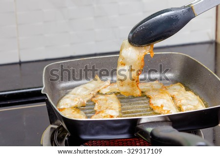 bacon being fried in a pan - stock photo