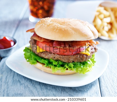 bacon cheeseburger meal with cola and fries - stock photo