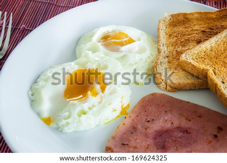 Bacon, fried eggs and toast on white plate - stock photo