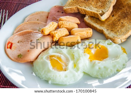 Bacon, fried eggs, sausage and toast on white plate - stock photo