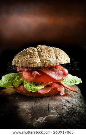 Bacon, lettuce and tomato meal, the Ultimate BLT. The perfect image for your restaurant or bistro menu designs. Shot in creative lighting in a rustic setting against a dark background. Copy space. - stock photo