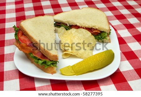 bacon, lettuce and tomato sandwich with potato chips and a pickle
