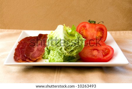Bacon Lettuce Tomato on a white plate 3 Strips of bacon with crisp lettuce and sliced tomato.