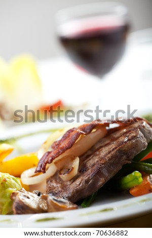 bacon on a steak with vegetables