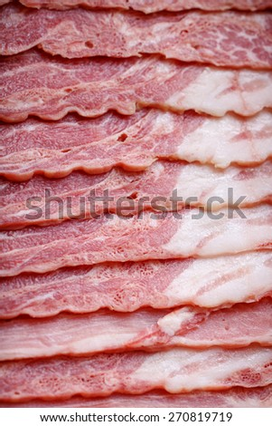 Bacon on the wooden background with salad leaves