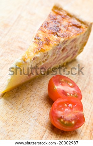 Bacon quiche with a tomato on a wooden board