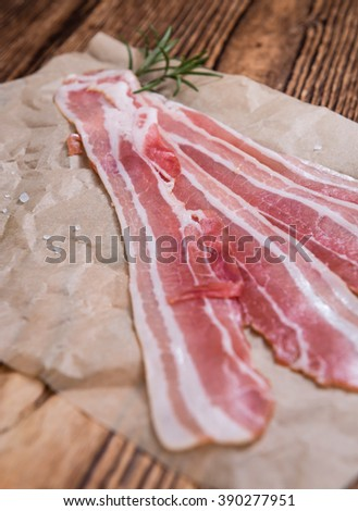 Bacon (raw) as detailed close-up shot on an old wooden table - stock photo