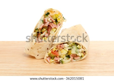 Bacon, salad and blue cheese filled bread wraps on a wooden board against a white background