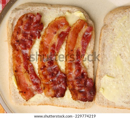 Bacon sandwich on buttered wholewheat bread. - stock photo