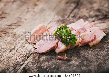 Bacon slices. Bacon with garnish on wooden table - stock photo