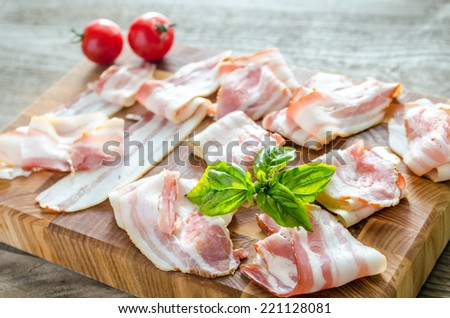 bacon strips on wooden board - stock photo