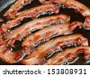 Bacon strips or rashers being cooked in frying pan. - stock photo