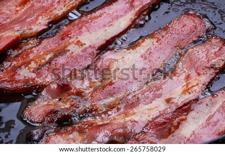 Bacon strips or rashers being cooked in frying pan - stock photo