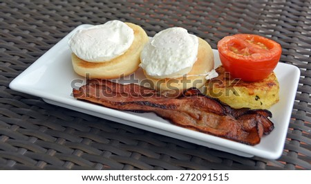 Bacon & two Poached  Eggs on a white plate with a  Hash Brown and a Tomato. - stock photo