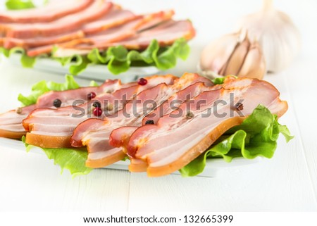 Bacon with dill and pepper on white wooden surface.