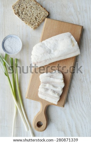 Bacon with onion and garlic on a wooden board.Salty spiced lard, Ukrainian cuisine