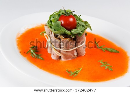 Bacon with sauce and vegetables on a plate - stock photo