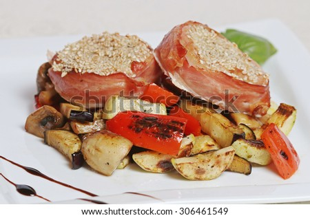 Bacon-Wrapped beef medallions with vegetables, selective focus - stock photo