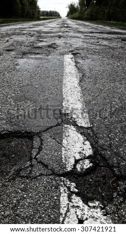 Bad asphalt road with white line. - stock photo