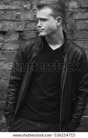 Bad boy concept. Portrait of brutal young man with short hair wearing black leather jacket, posing over brick wall background. Hands in pockets. Grunge style. Monochrome outdoor shot