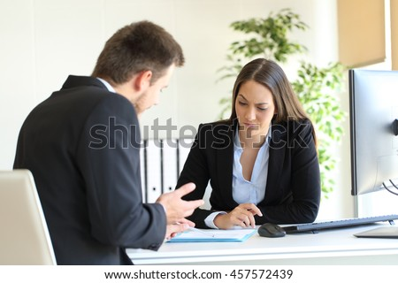 Bad businessman trying to convince to a suspicious client during a difficult negotiation in a desktop at office - stock photo