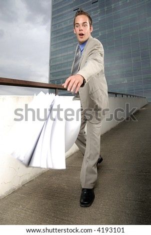 Bad day - fumbler businessman with mobile phone in front of modern business building.