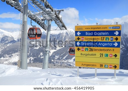 BAD GASTEIN, AUSTRIA - MARCH 10, 2016: People ride gondolas of cable car in Bad Gastein. It is part of Ski Amade, one of largest ski regions in Europe with 760km of ski runs. - stock photo