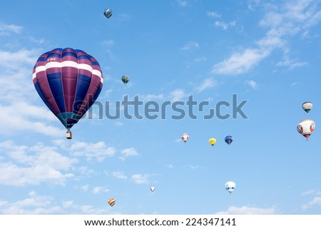 BAD GRIESBACH, GERMANY - AUGUST 22: Hot air ballon festival at Bad Griesbach, Germany on August 22, 2014. More than 6000 visitors watched over 20 ballons. Foto taken from the public Kurwiese park. - stock photo