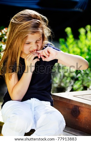 Bad habits - young girl biting her nails - stock photo