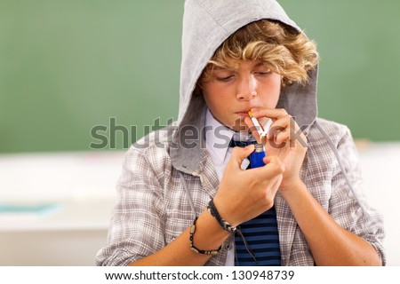 bad high school teen boy lighting cigarette in classroom - stock photo