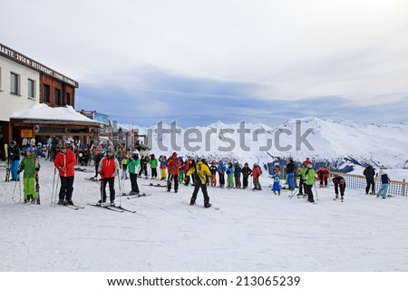 BAD HOFGASTEIN, AUSTRIA - JANUARY 09, 2013: Unidentified skiers and ski instructor with team of children at slope in the Austrian Alps on famous ski resort Bad Hofgastein, Austria. - stock photo