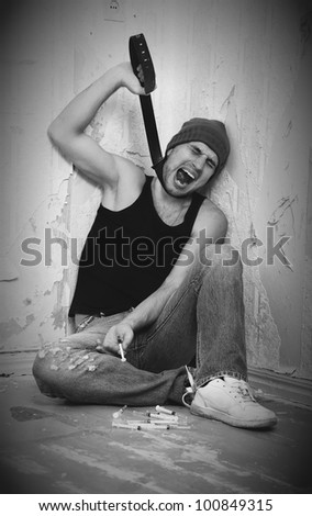 bad man - addict with syringes and  with drugs sitting on the floor - stock photo