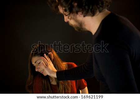 Bad man slapping woman in face in the dark - stock photo