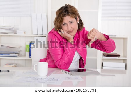Bad mood: woman in the office with thumb down - stock photo