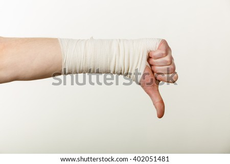 Bad news and information. Medicine aspects. Male hand with bandage showing thumb down sign symbol. - stock photo