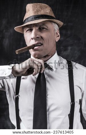 Bad news for you. Bossy senior man in hat and suspenders smoking cigar and holding finger on his neck while standing against dark background  - stock photo