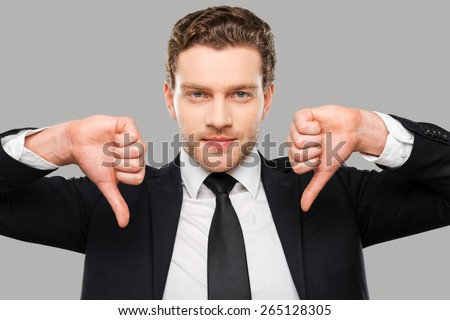 Bad news for you. Confident young man in formalwear showing his thumbs down and looking at camera while standing against grey background - stock photo