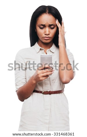 Bad news. Frustrated young African woman holding mobile phone and looking at it while standing against white background - stock photo