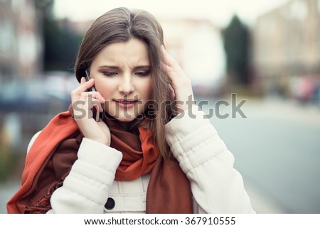 Bad news. Sad woman on phone. Closeup portrait headshot of beautiful upset unhappy, serious girl student talking on mobile cityscape outdoor background. Multicultural, mixt race, asian russian model - stock photo