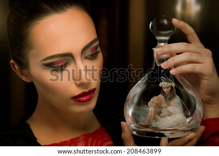 Bad queen keeping little fairy in the bottle - stock photo