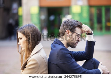 Bad relationship concept. Man and woman in disagreement. Young couple after quarrel sitting back to back. Outdoor  - stock photo