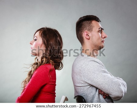 Bad relationship concept. Man and woman in disagreement. Young couple after quarrel sitting on chairs back to back - stock photo