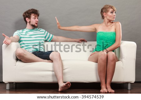 Bad relationship concept. Man and woman in disagreement. Young couple sitting on couch at home having quarrel, offended wife and unhappy husband