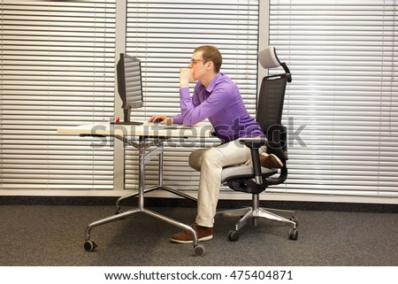 bad sitting posture at workstation - man at office work