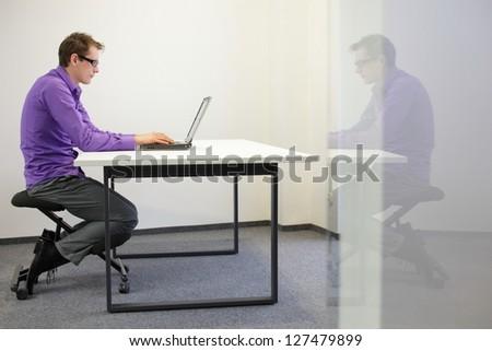 bad sitting posture at workstation. man on kneeling chair - stock photo
