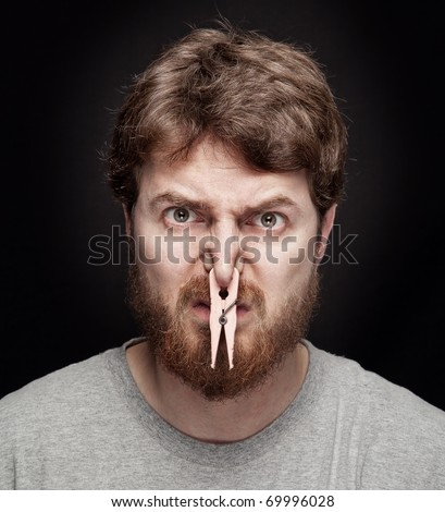 Bad smell concept - peg on male nostrils over black - stock photo