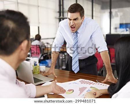 bad-tempered caucasian business executive yelling at two asian subordinates in office. - stock photo