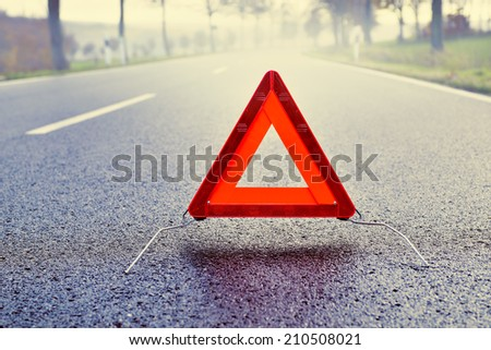 Bad Weather Driving - Warning Triangle on a Misty Road - stock photo